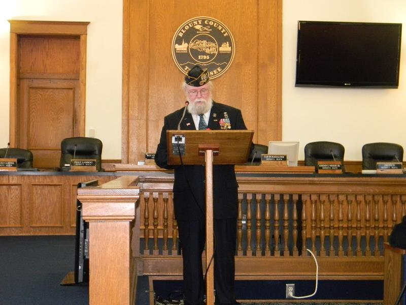 Man with beard and glasses stands in suit with medals on lapel and hat, speaking at podium